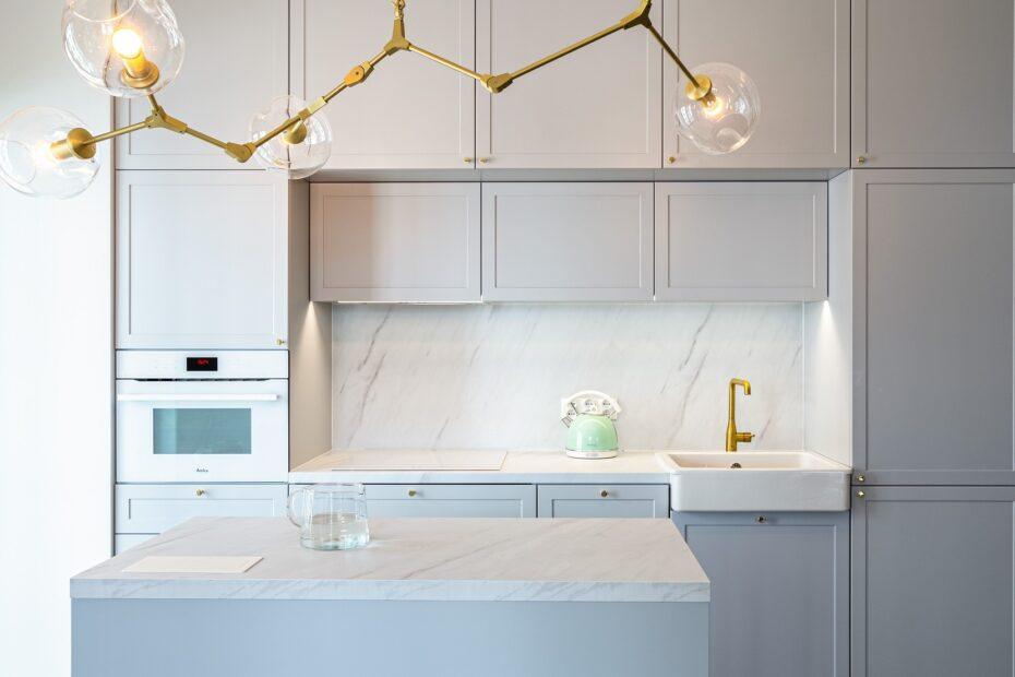 Dizajnerska, złota lampa w minimalistycznej kuchni na wymiar