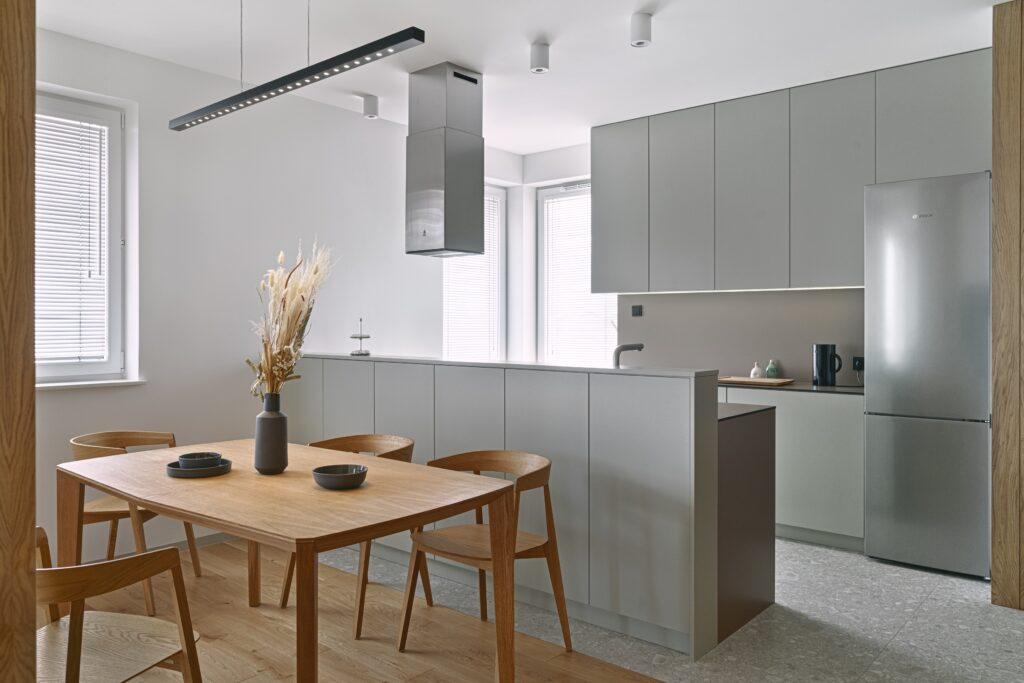 Drewniany stół i krzesła w minimalistycznej szarej kuchni