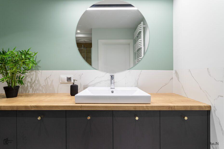 Duże okrągłe lustro w łazience wraz z jasnym blatem i ciemnymi meblami w zabudowie