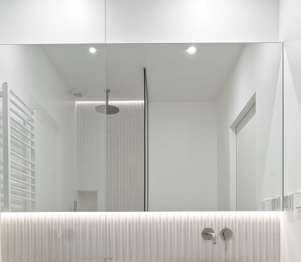 Duże lustro w jasnej łazience, a w tle kabina prysznicowa z srebrną deszczownicą