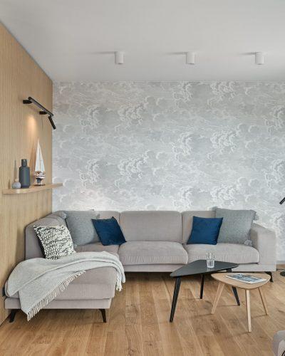 Szara kanapa na czarnych nóżkach w minimalistycznym wnętrzu