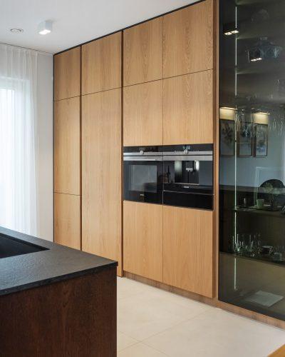 Przestrzenna kuchnia z jasnymi meblami i kuchenką w zabudowie